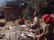 Local women grinding concretes for community project on April 2010