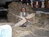 Woman from Pangkarma village webbing wheat